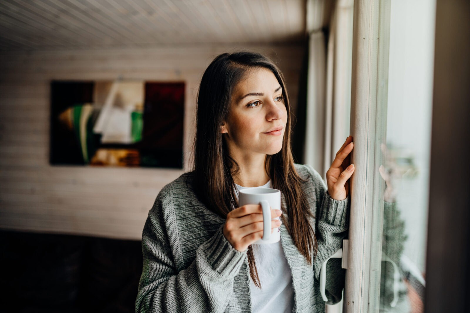 Girl with mug stares thoughtfully out of a window