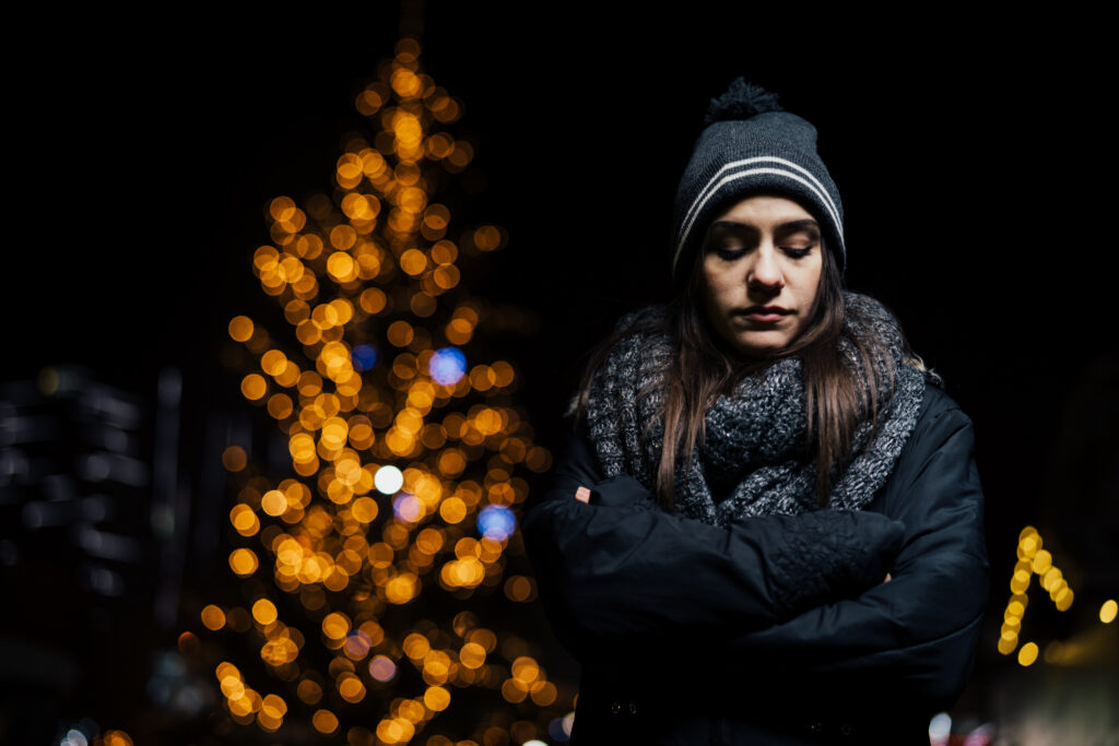 Night portrait of a sad woman feeling alone and depressed in winter.Winter depression and loneliness concept