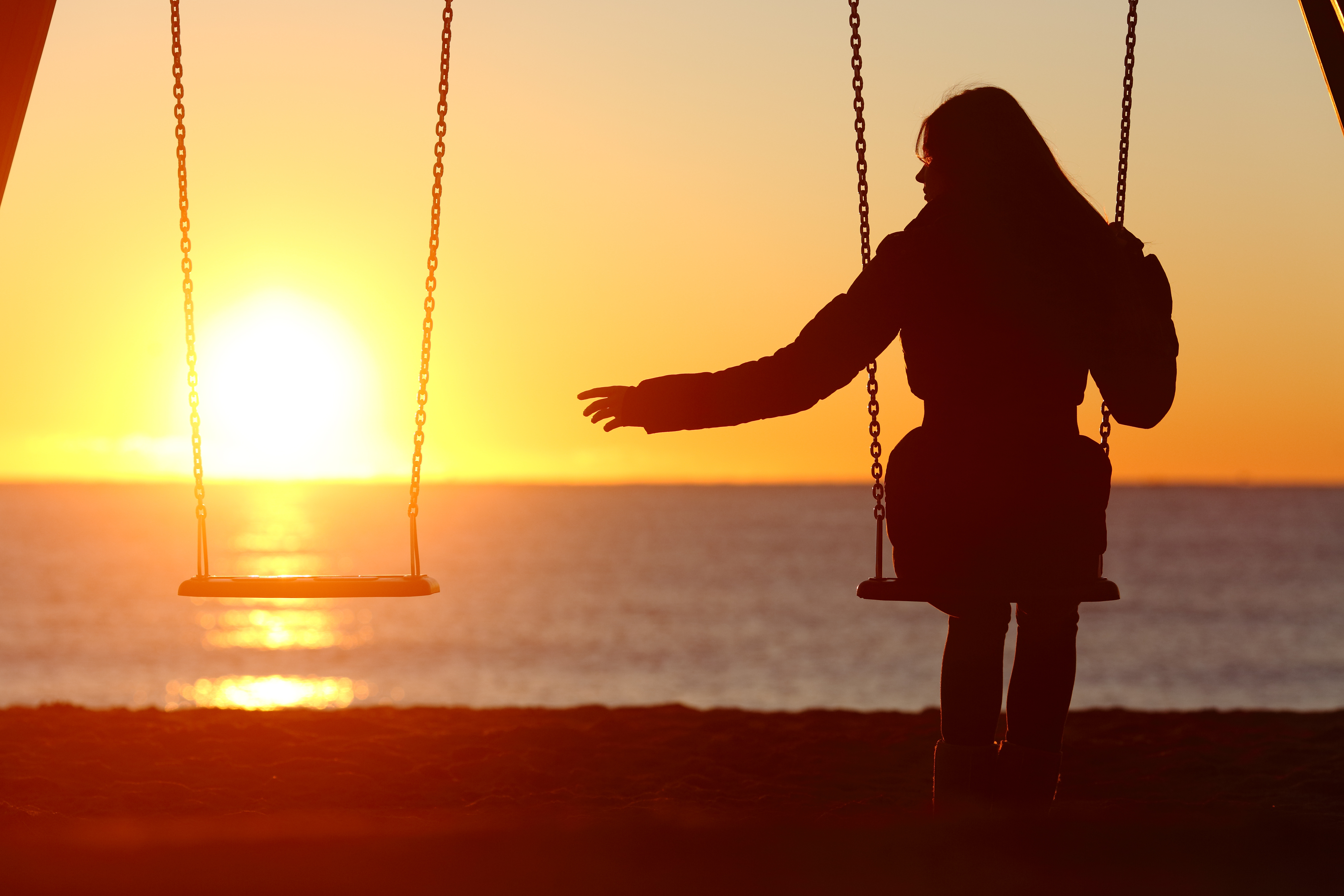 Bereaved woman alone missing a partner while swinging on the beach at sunset