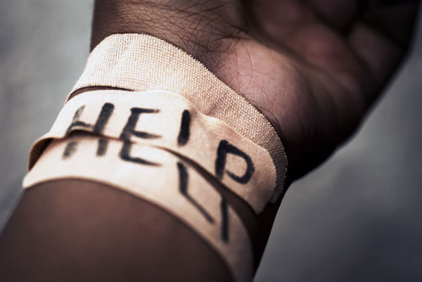 A bandaged wrist withthe word 'help' written on the bandage