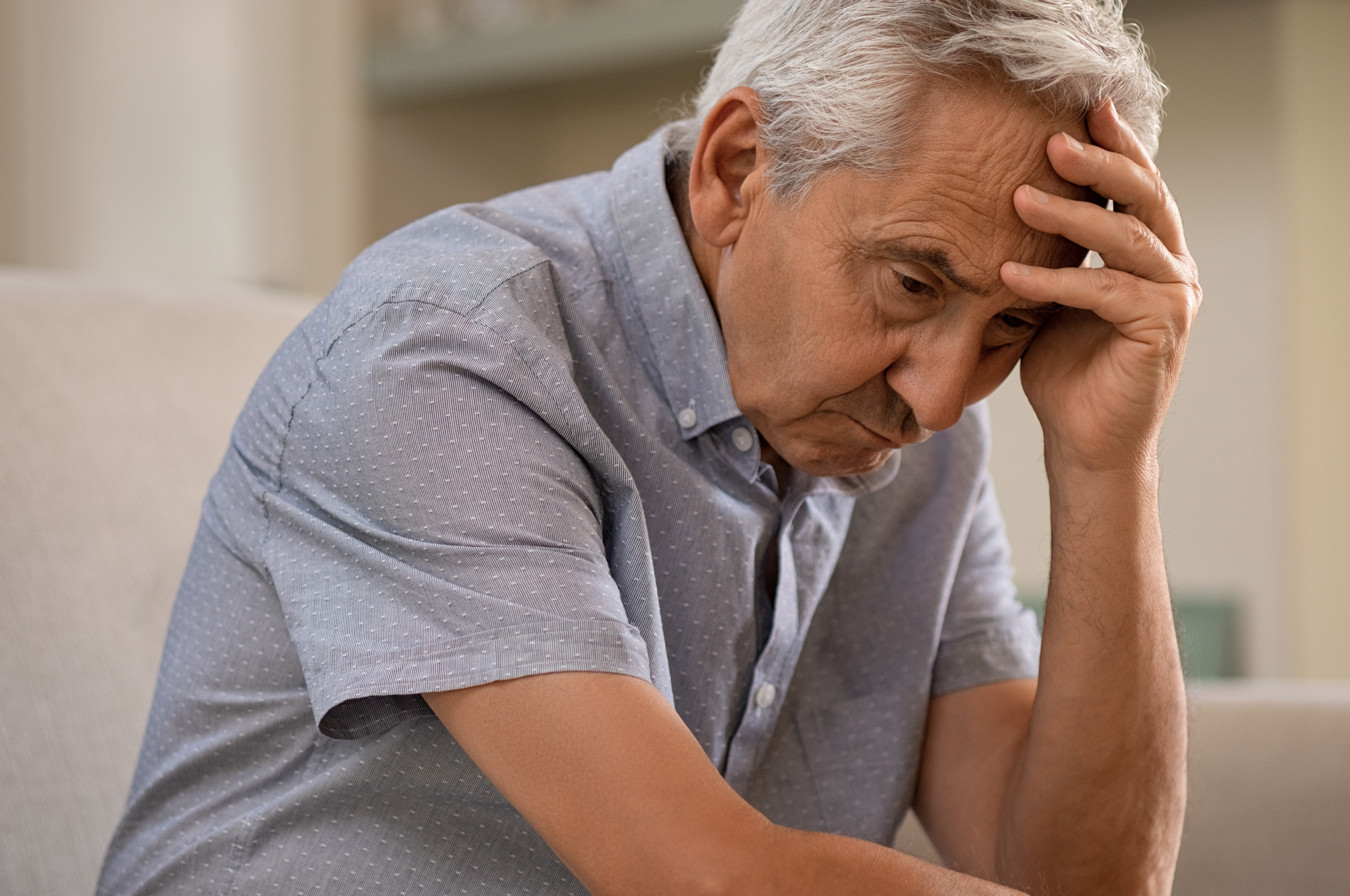 Thoughtful senior man sitting on couch. Depressed sad man sitting with hand on head thinking while looking away.